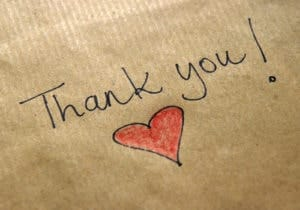 thank you message handwritten on piece of paper with heart symbol